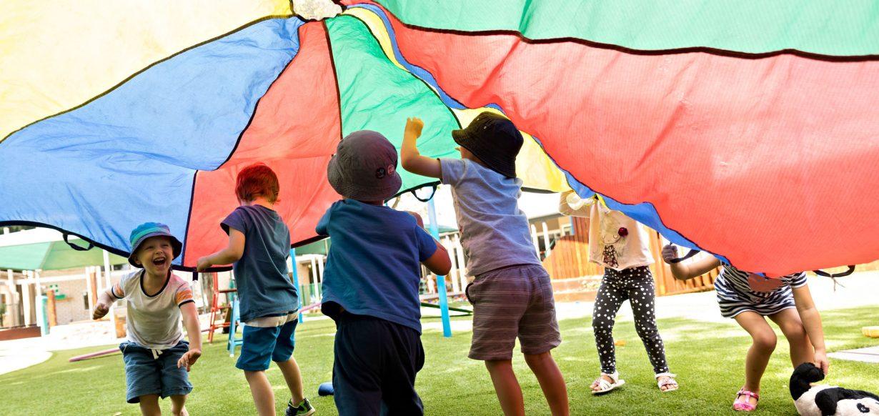 children running under parachute at Lizards ELC