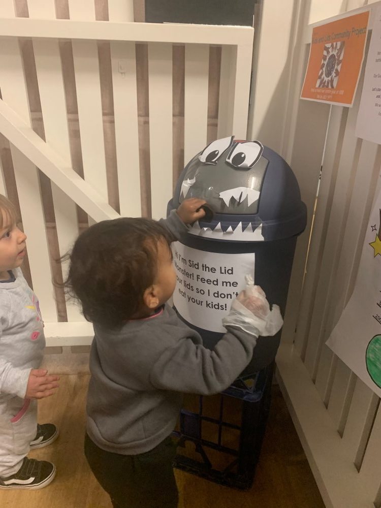 toddler adding plastic lids to Sid the Lid Monster bin