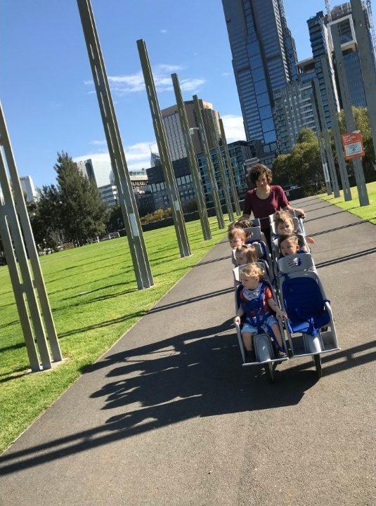 educator pushing octo-pram on daily excursions