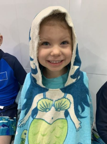young child in mermaid towel at swimming lessons