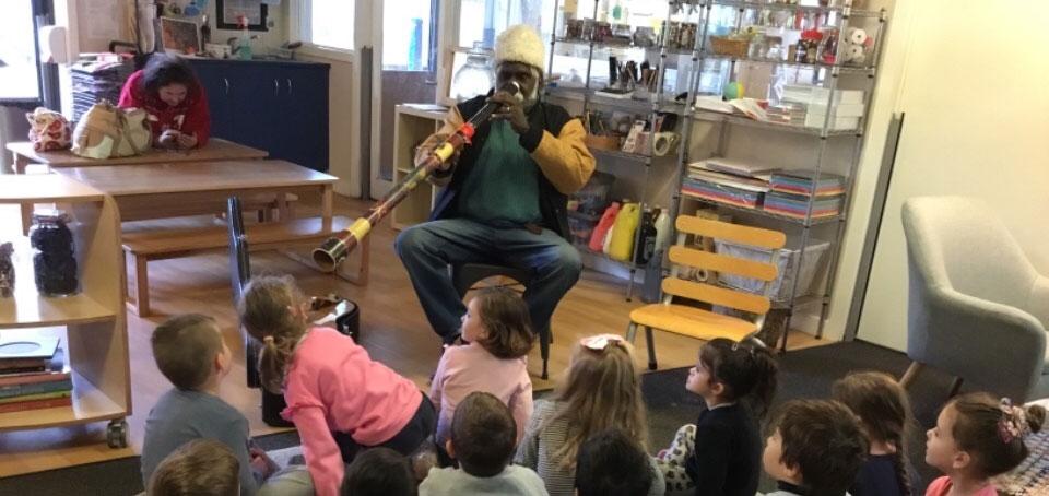 member of Aboriginal performance troupe plays didgeridoo to children