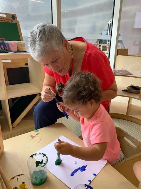intergenerational partnership: nanna rita painting with child