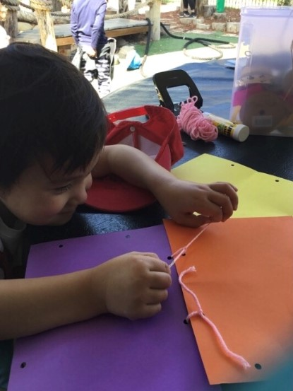 child threading string through cardboard for friendship quilt