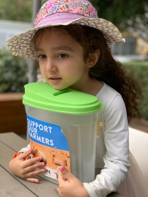girl holding donation box for farmers fundraiser