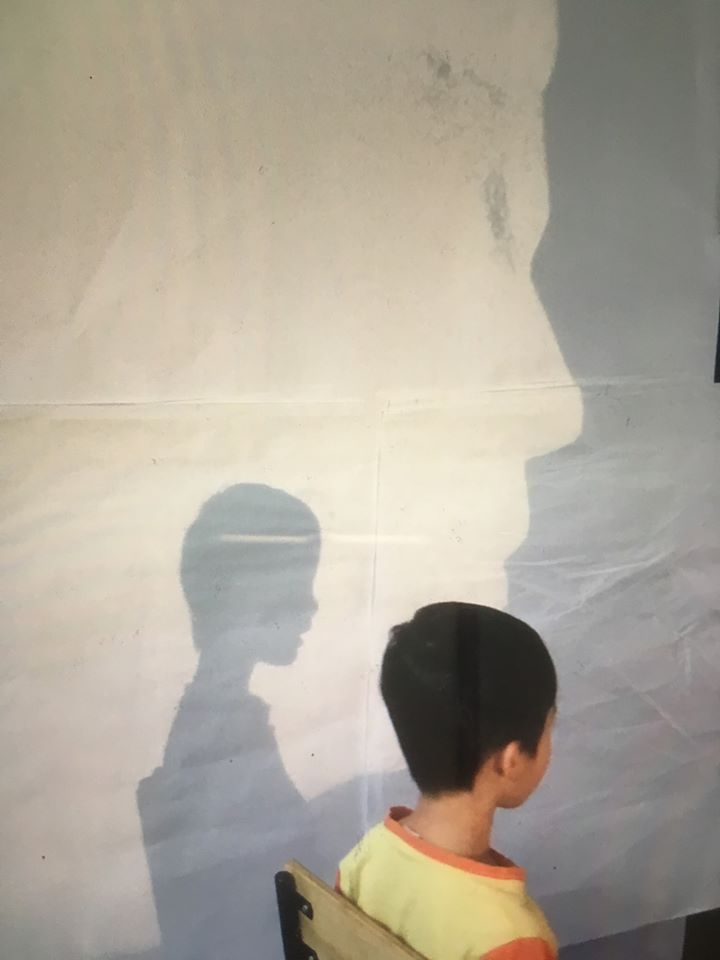 child sitting in front of projector to get his shadow traced during Summer Rain program