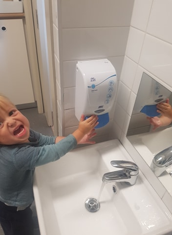 child using soap dispenser as part of hand washing routine