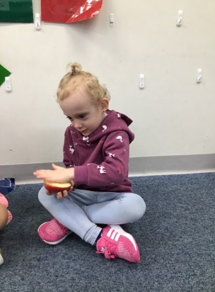 child rubbing dirty hands on apple for germs experiment