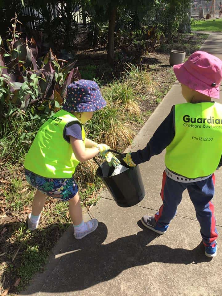 Children at Altona North wearing safety vests and holding bucket of rubbish