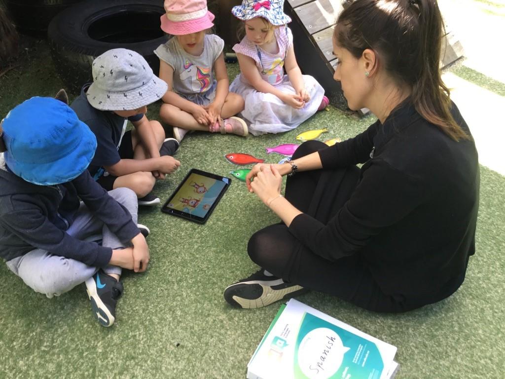 children sitting with Educator learning Spanish through ELLA program on ipad