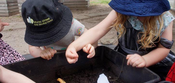 children exploring their curiosity with worm farm