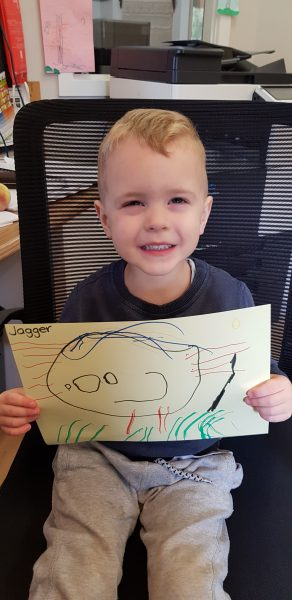 child holding drawing he made for doctors and nurses