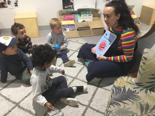 Educator reading Hi. This is coronavirus. book to children