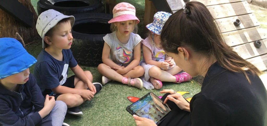 children sitting with Educator learning Spanish through ELLA program