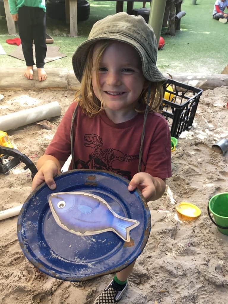 child wearing a hat and holding a plate with a plastic fish on it