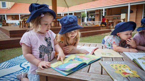 Children reading books outside at Balmain Cove